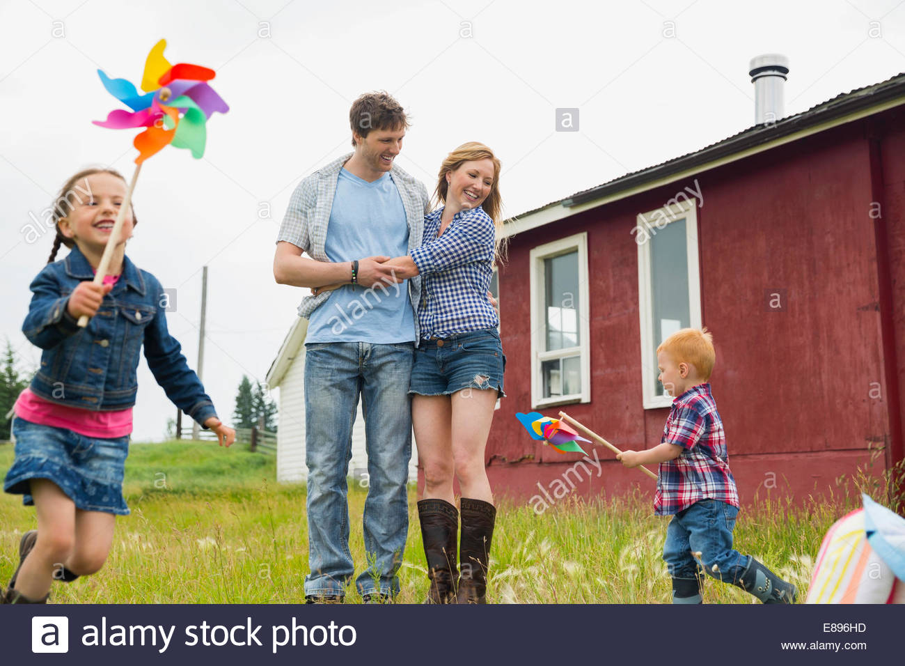 Parents watching children play with pinwheels Stock Photo