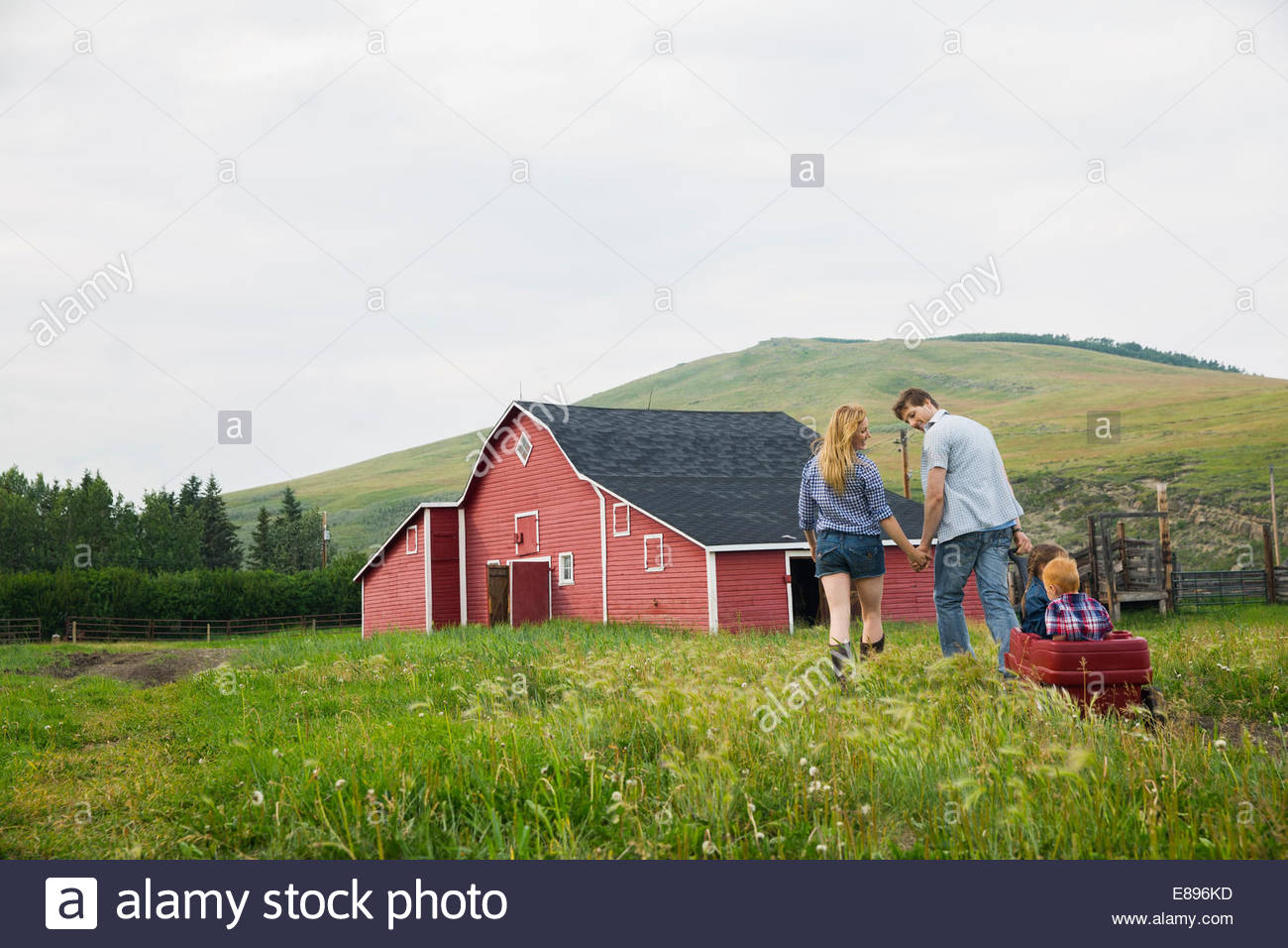 Parents pulling children in wagon outside barn - Stock Image