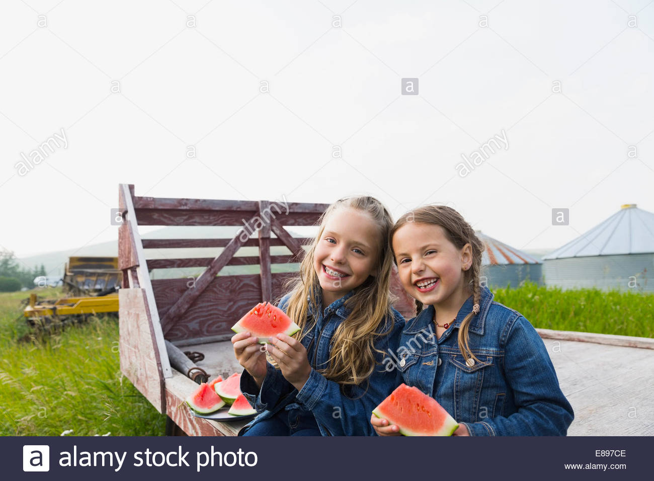 Portrait of smiling girls eating watermelon on farm - Stock Image