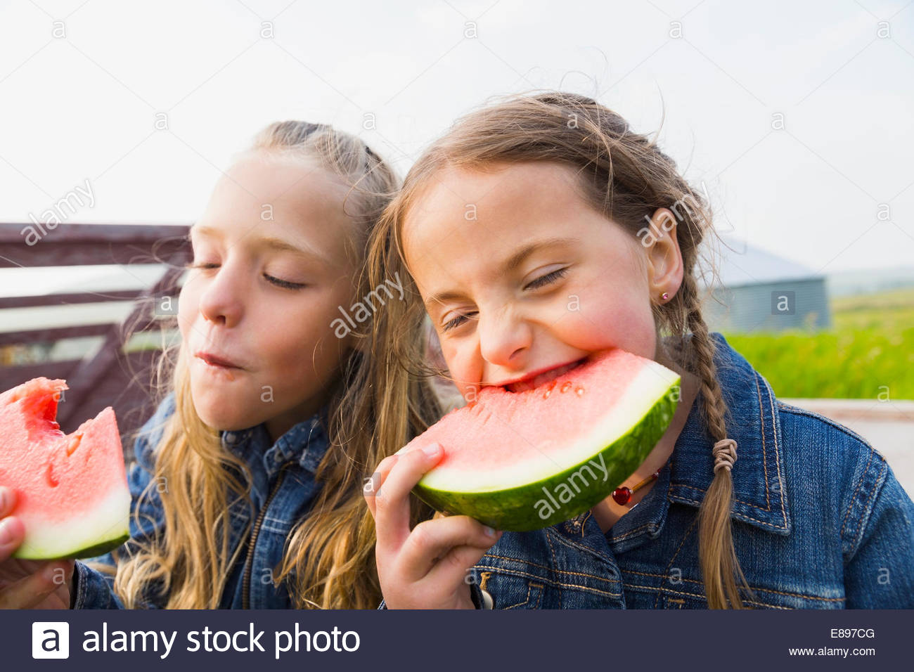 Girls biting into watermelon - Stock Image