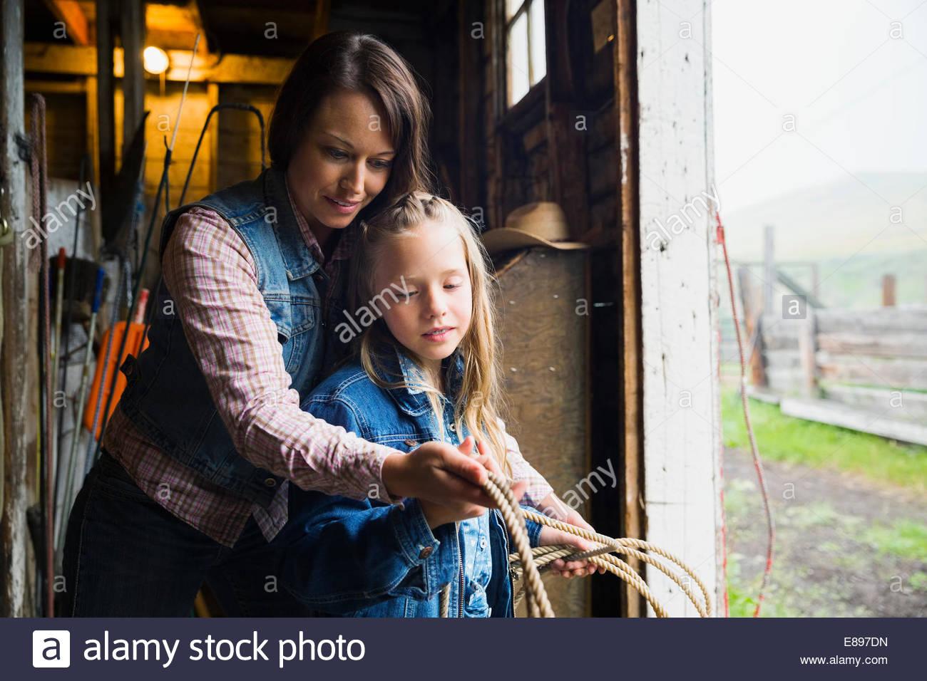 Mother teaching daughter to lasso in barn doorway - Stock Image