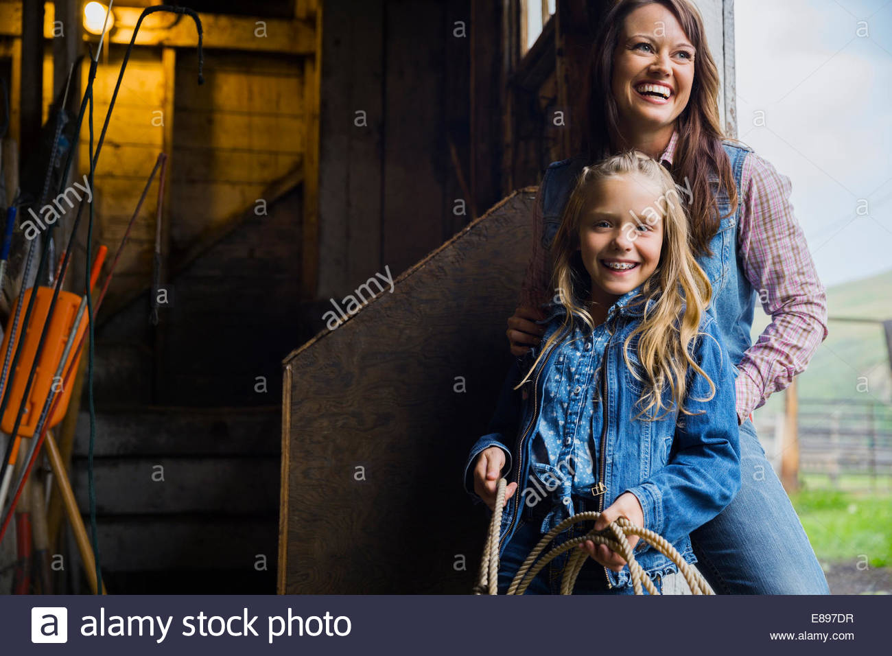 Mother and daughter laughing in barn doorway Stock Photo