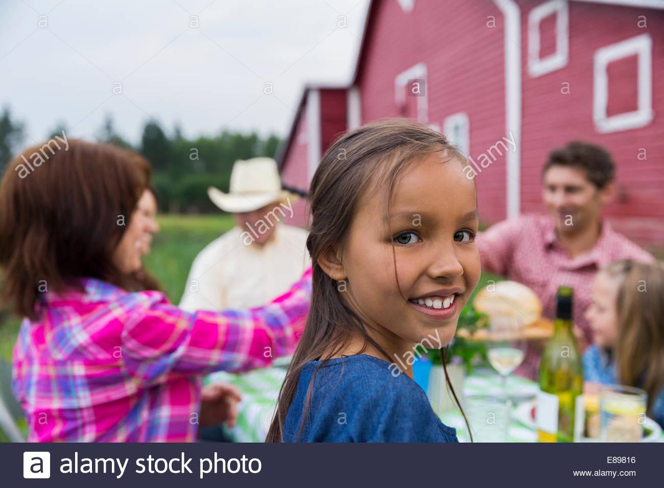 Portrait of girl enjoying family dinner outside barn - Stock Image