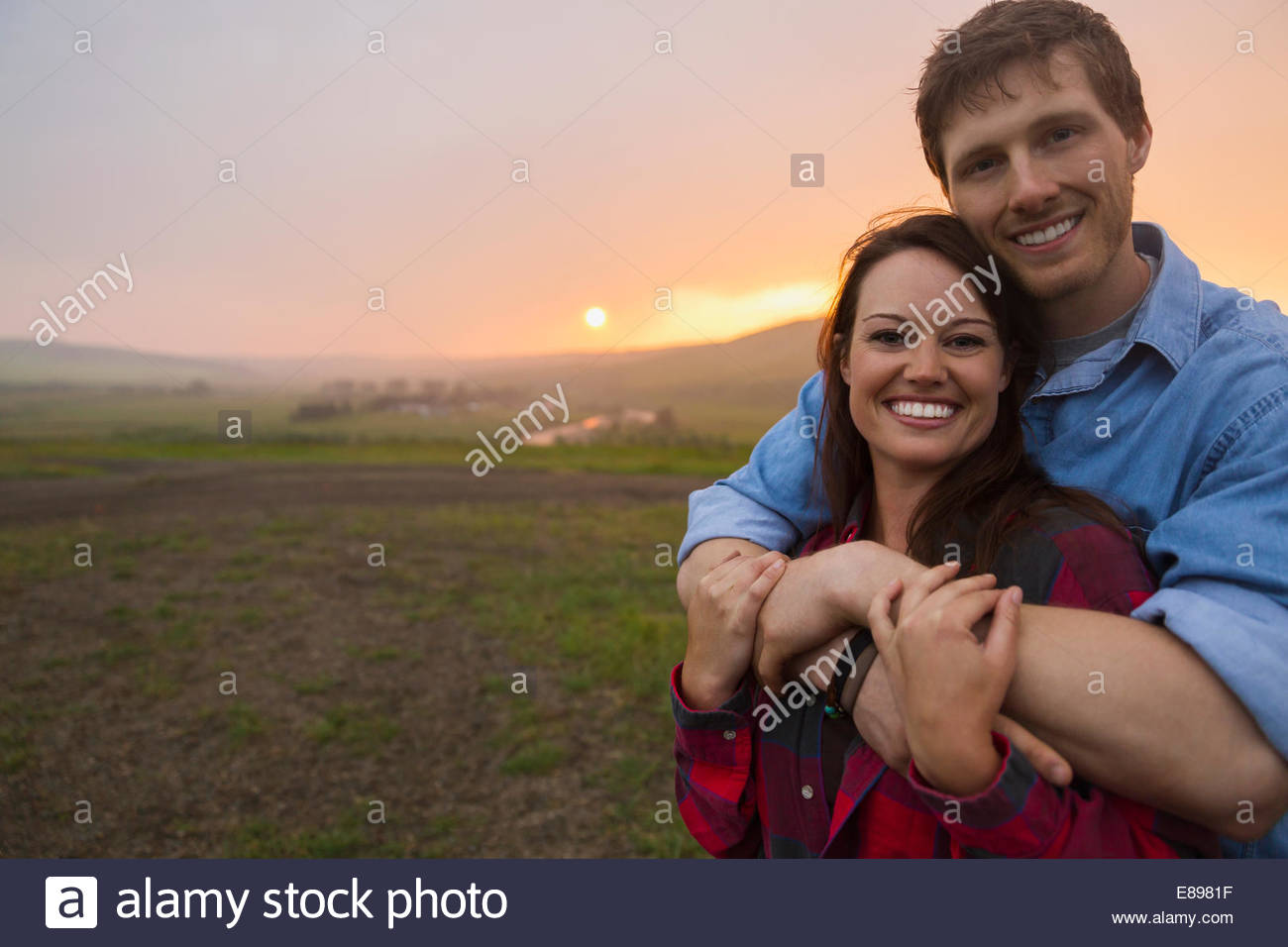 Portrait of couple hugging in field at sunset - Stock Image