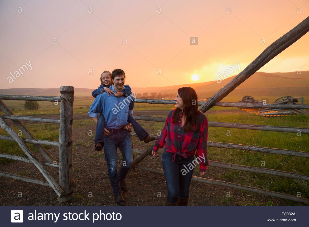 Family walking through pasture gate at sunset - Stock Image