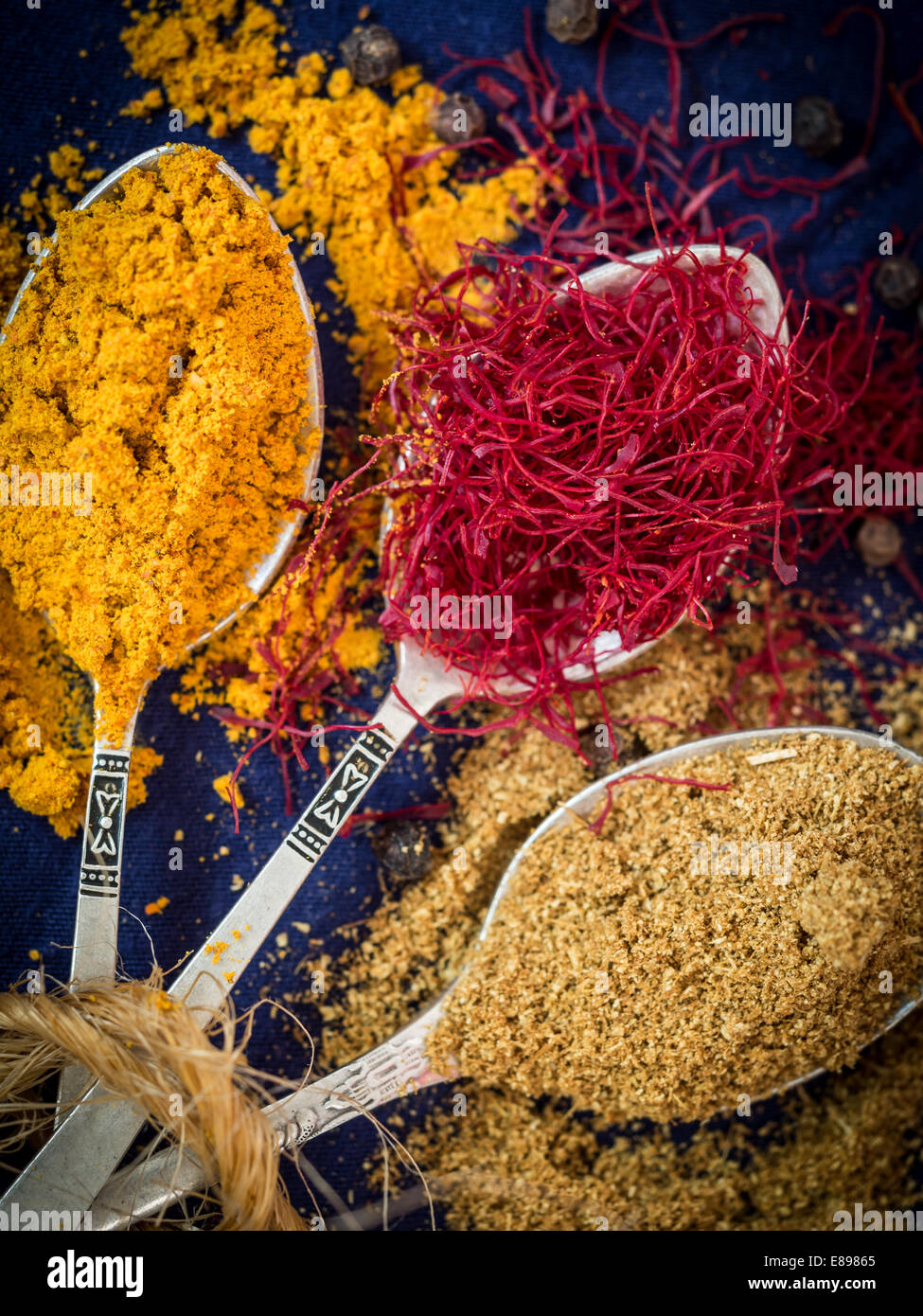 Three silver spoons with spices from Zanzibar: turmeric, saffron and cumin. Vertical orientation, dark blue background. - Stock Image