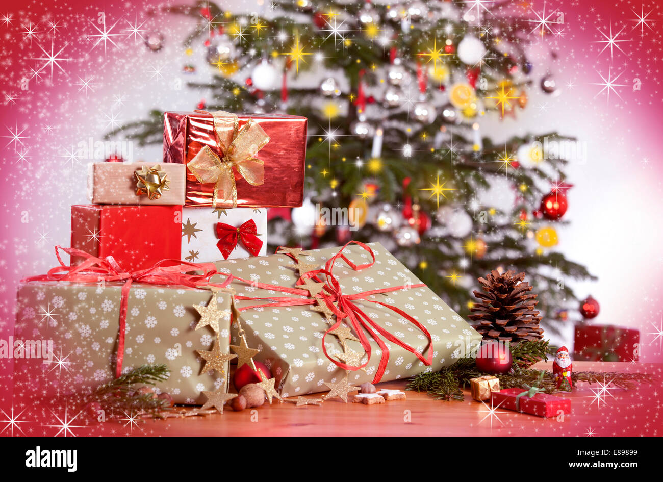 many gifts on a table and christmas tree with red glittering background - How Many Gifts For Christmas