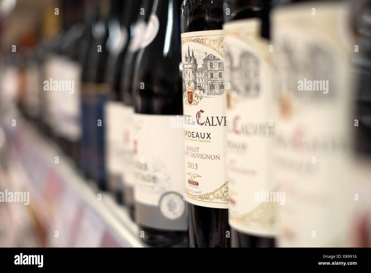A selection of red wine bottles on a shelf in a branch of Sainsbury's supermarket showing prices & offers - Stock Image