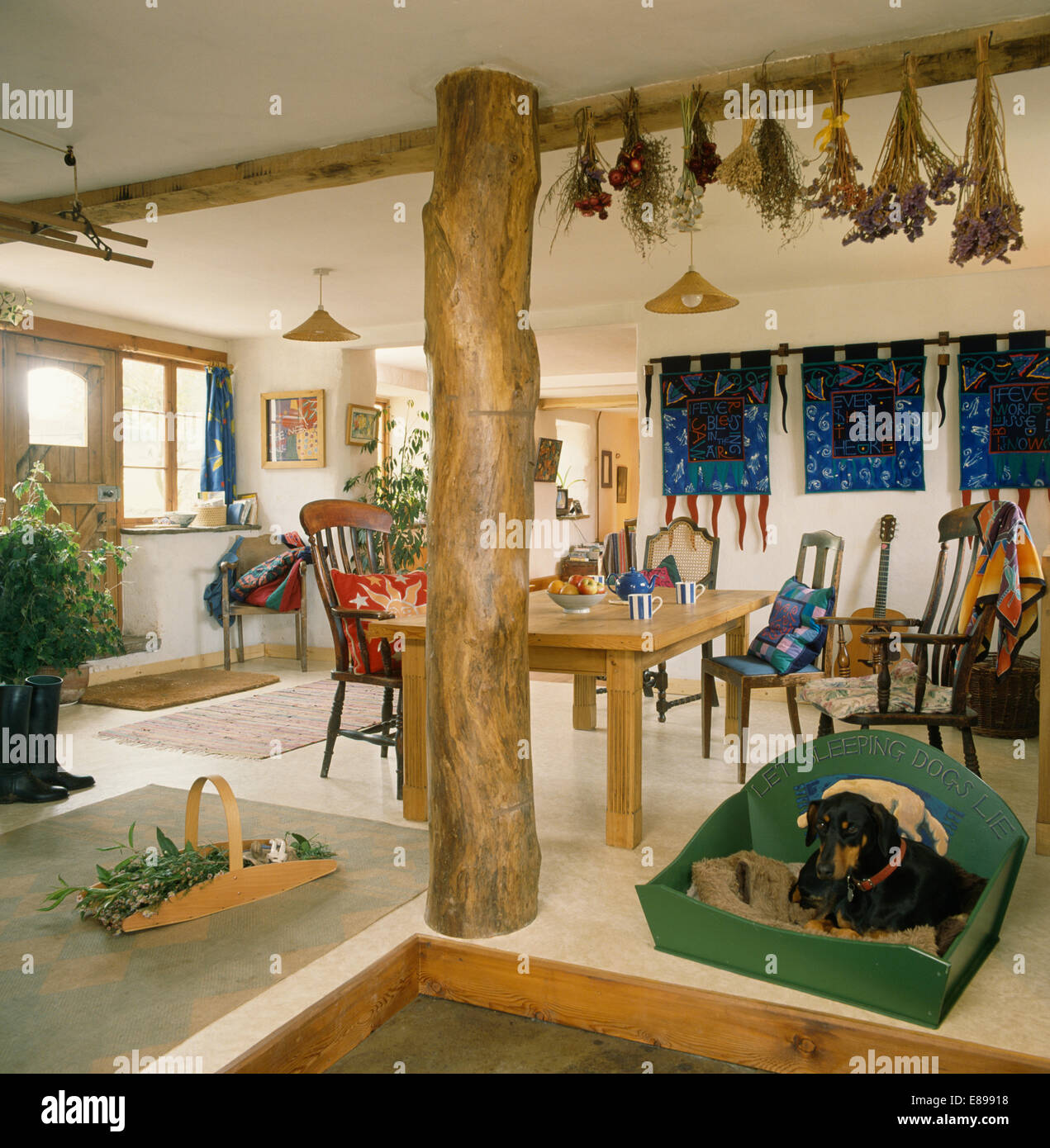 Rustic upright beam in eighties cottage dining room with dog in basket - Stock Image