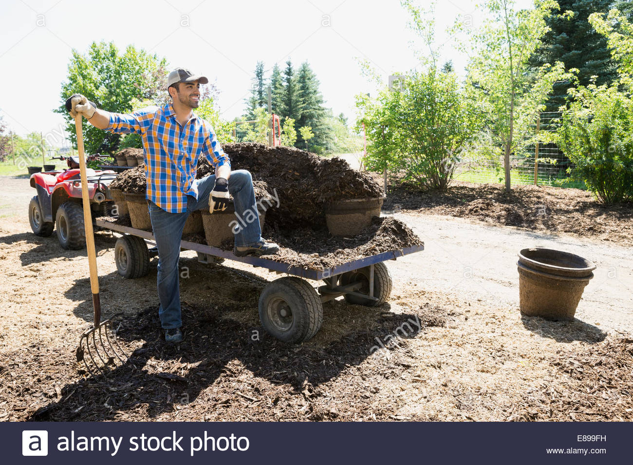 Smiling worker tilling dirt in garden - Stock Image