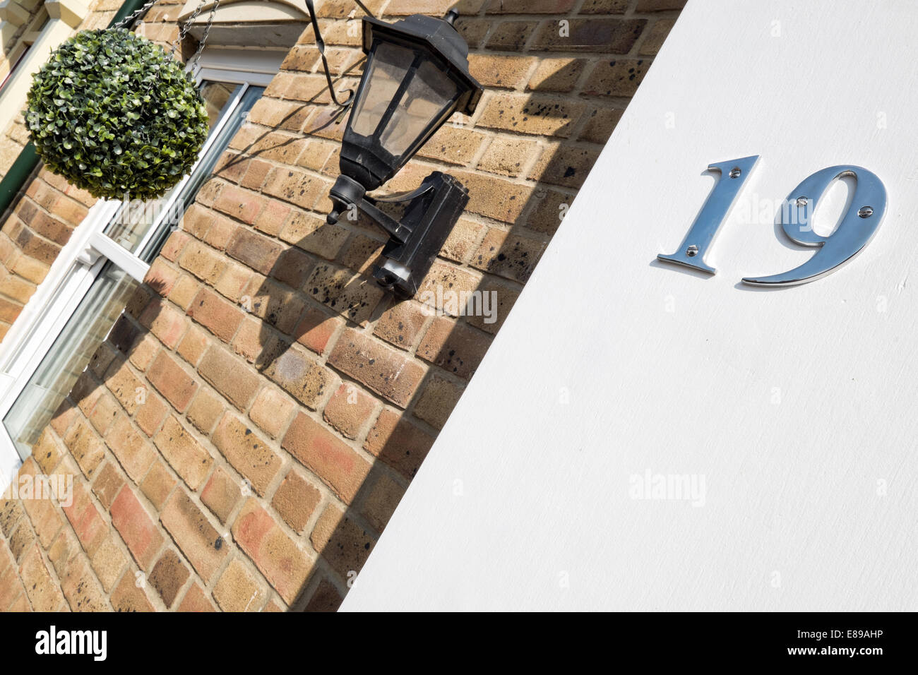 A chrome number 19 on a white stucco wall, used to identify the home's address - Stock Image