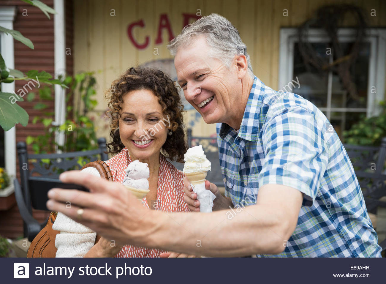 Couple with ice cream taking selfie outside cafe Stock Photo