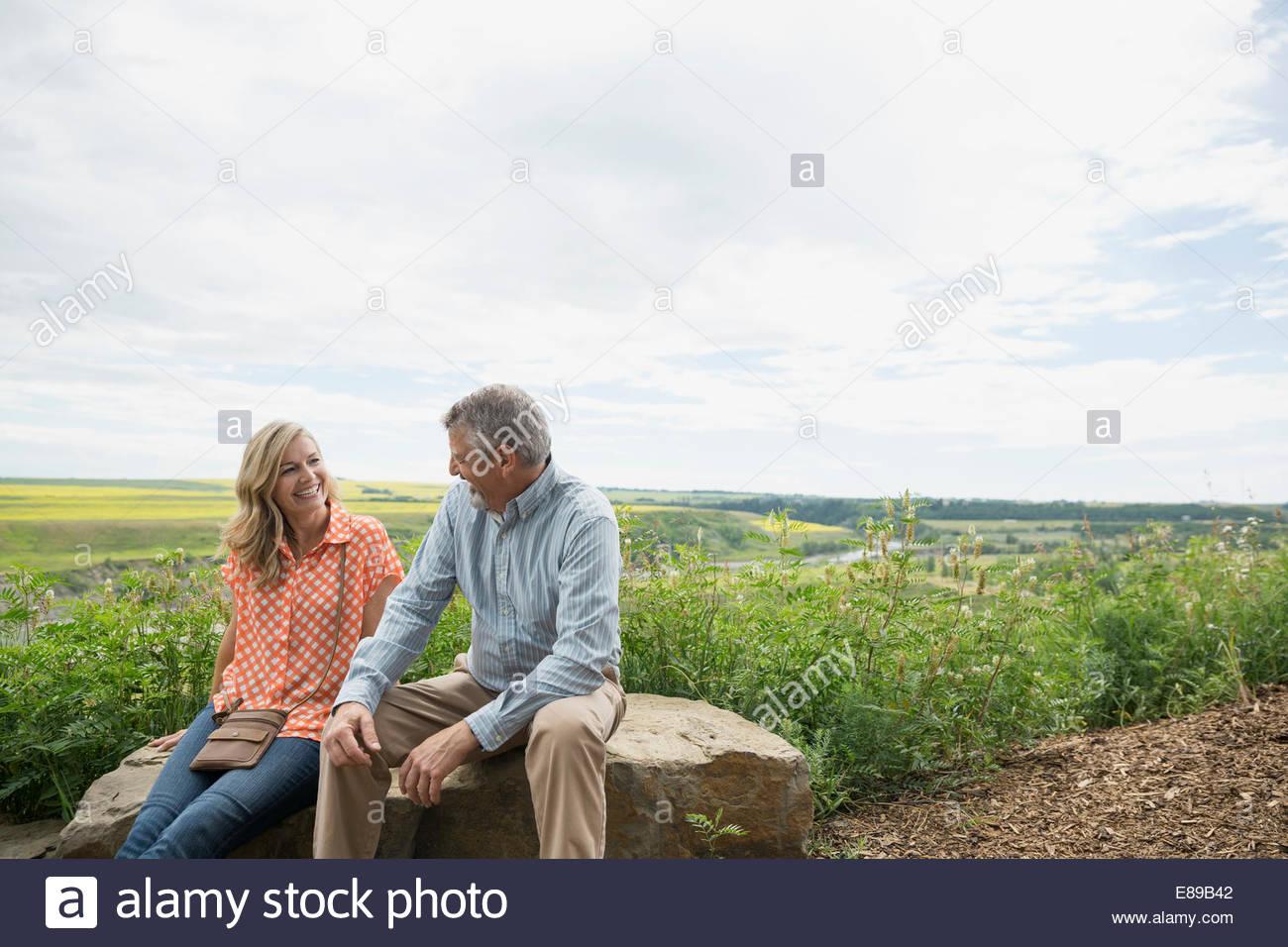 Couple sitting on rock overlooking countryside - Stock Image