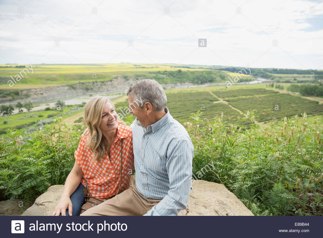 Smiling couple hugging on rock overlooking countryside - Stock Image