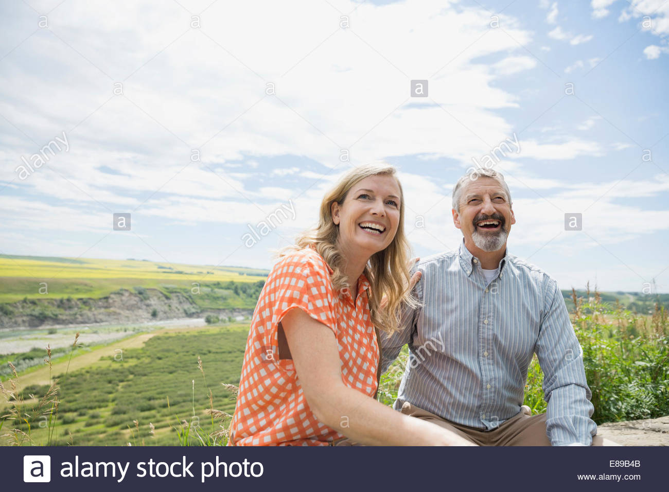 Couple laughing outdoors with countryside in background Stock Photo