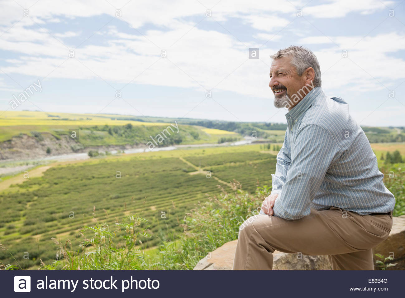 Smiling man looking at view of countryside - Stock Image