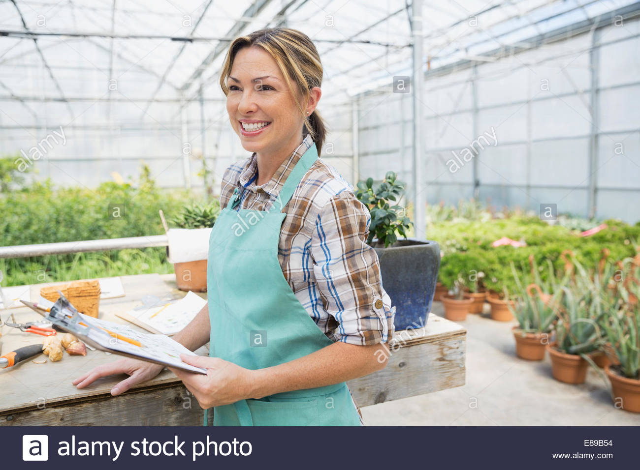 Smiling worker with clipboard in greenhouse - Stock Image