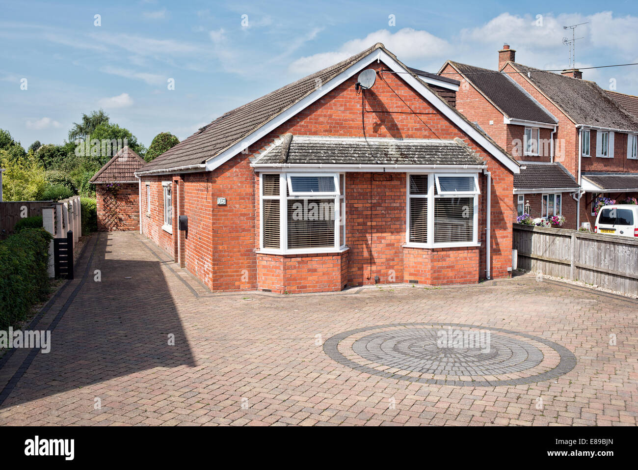 A renovated & extended, double glazed, red brick bungalow with block paved forecourt  on a sunny day, Wiltshire, - Stock Image