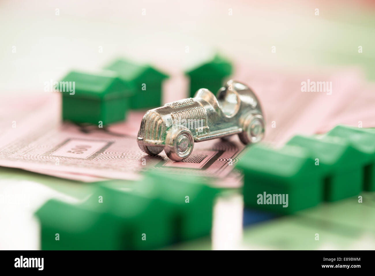 The Monopoly car game piece on yhe games' money with defocused houses on th board - Stock Image