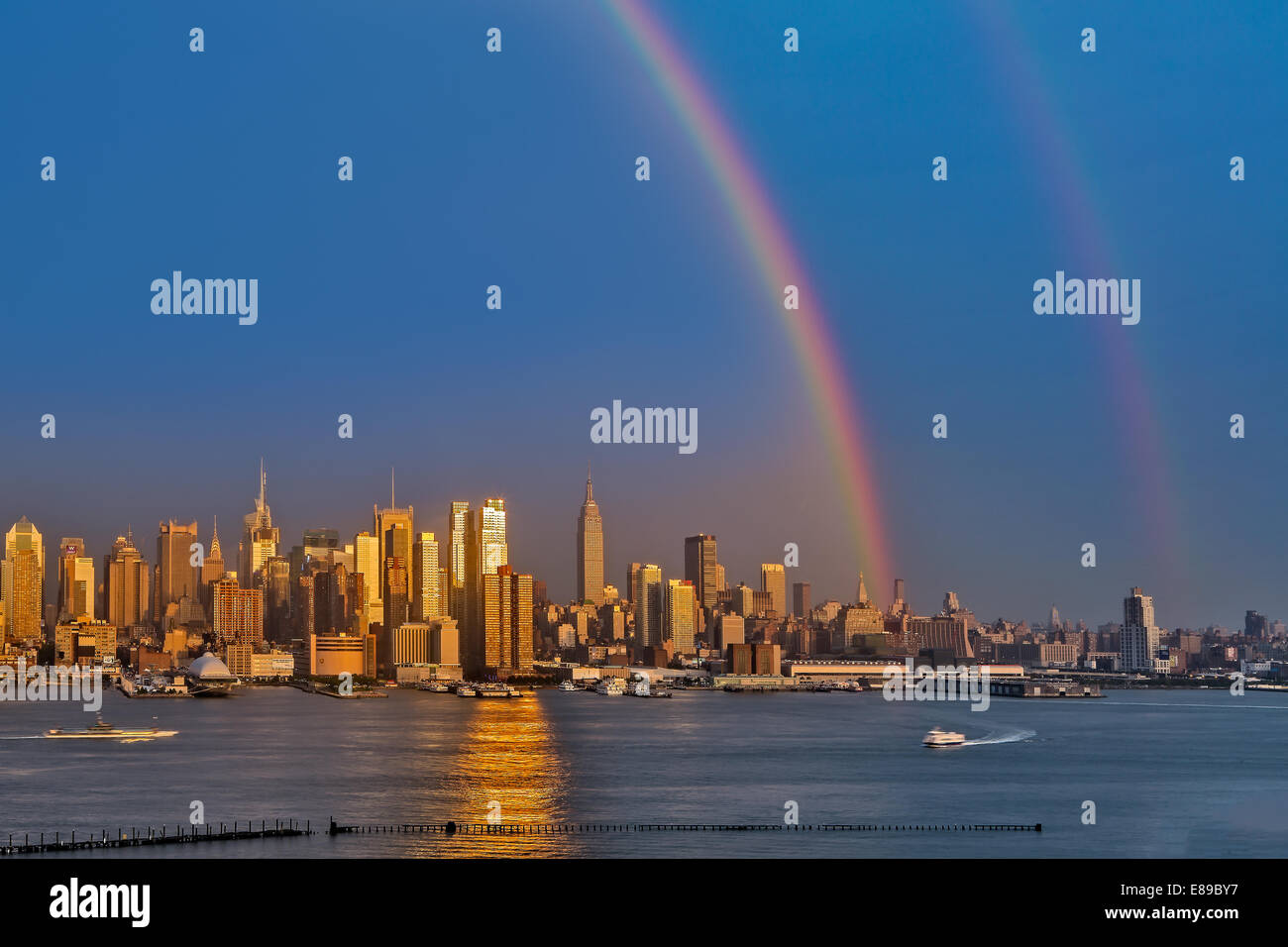 Double Rainbows emerge after a summer rain shower over the New York City Skyline at sunset. - Stock Image