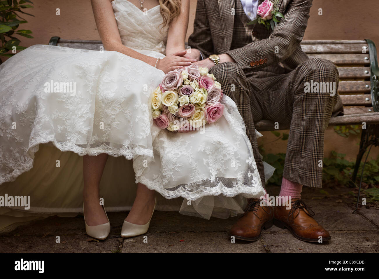 A bride & groom wearing a vintage style tweed suit& 50's style wedding,sitting on a bench, holding hands - Stock Image