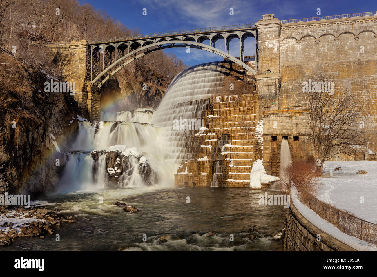 New Croton Dam waterfall also known as the Cornell Dam during a cold winter afternoon with a rainbow over the falls. - Stock Image