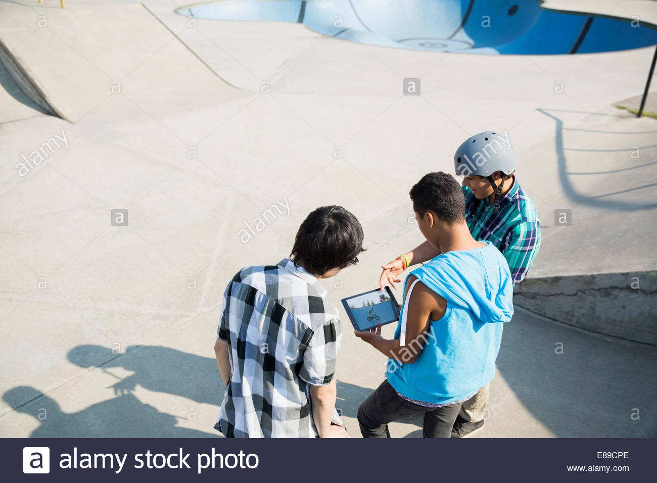 Teenage boys with digital tablet at skateboard park - Stock Image