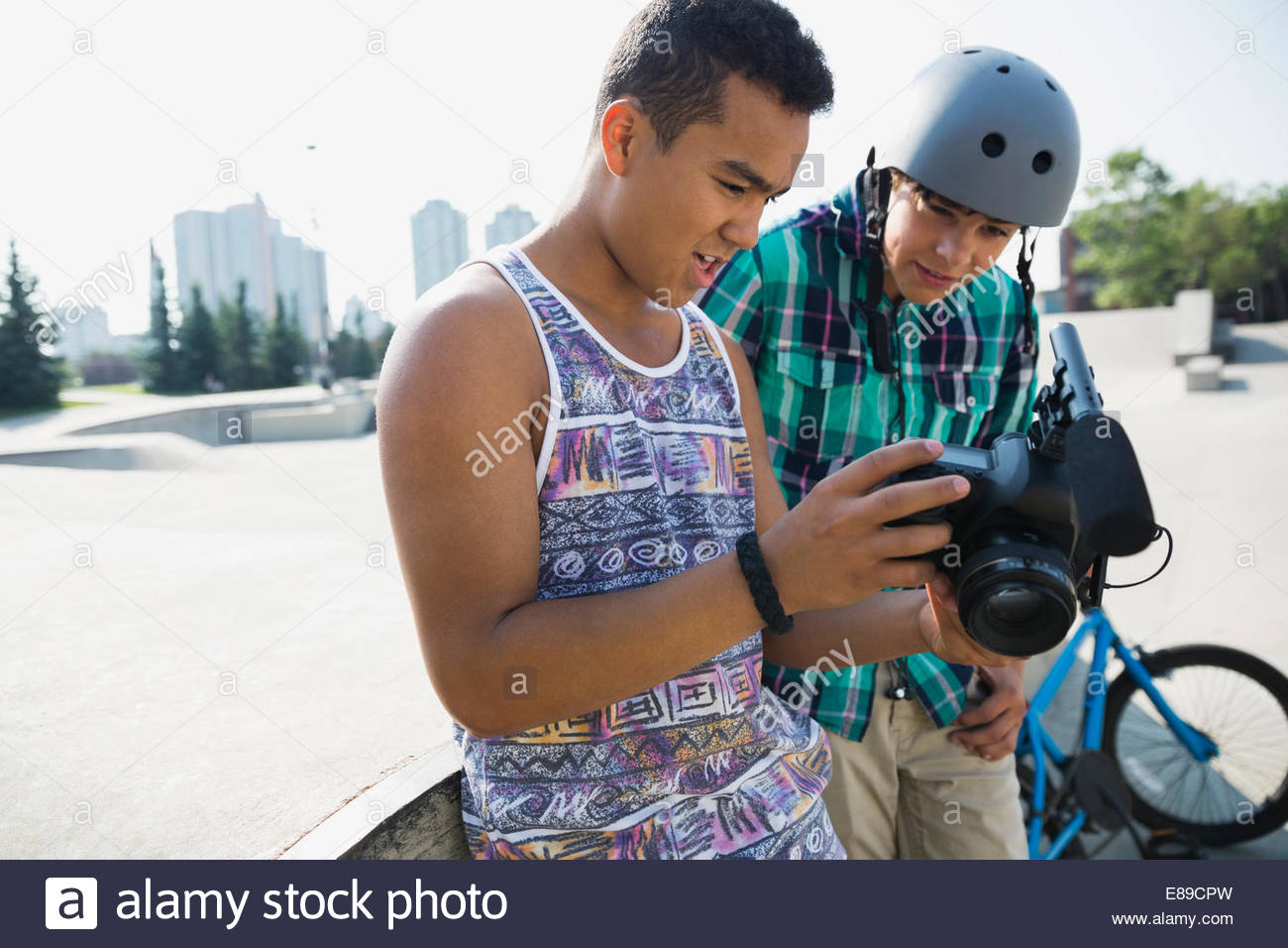 Teenage boys with camera at skateboard park - Stock Image