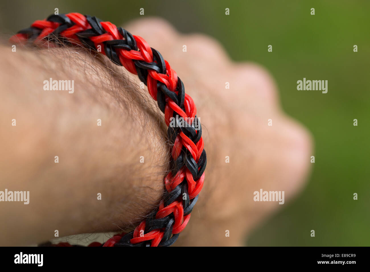 A red and black bracelet made from loom bands on a man's wrist. Model Released. - Stock Image