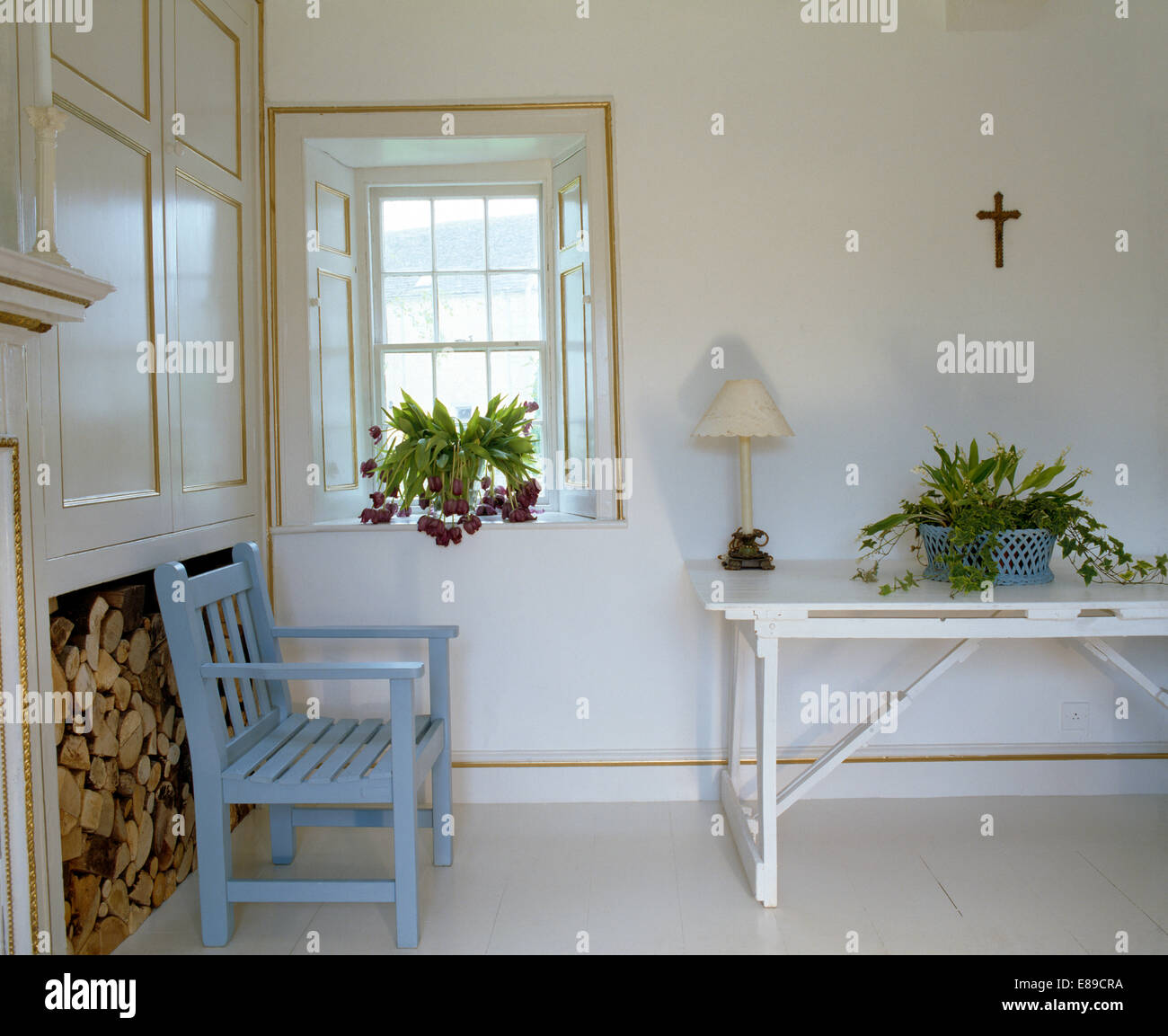 pale blue painted chair in front of recess piled with logs in stock rh alamy com