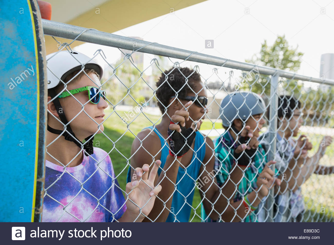 Portrait of teenage boys with skateboard at fence - Stock Image