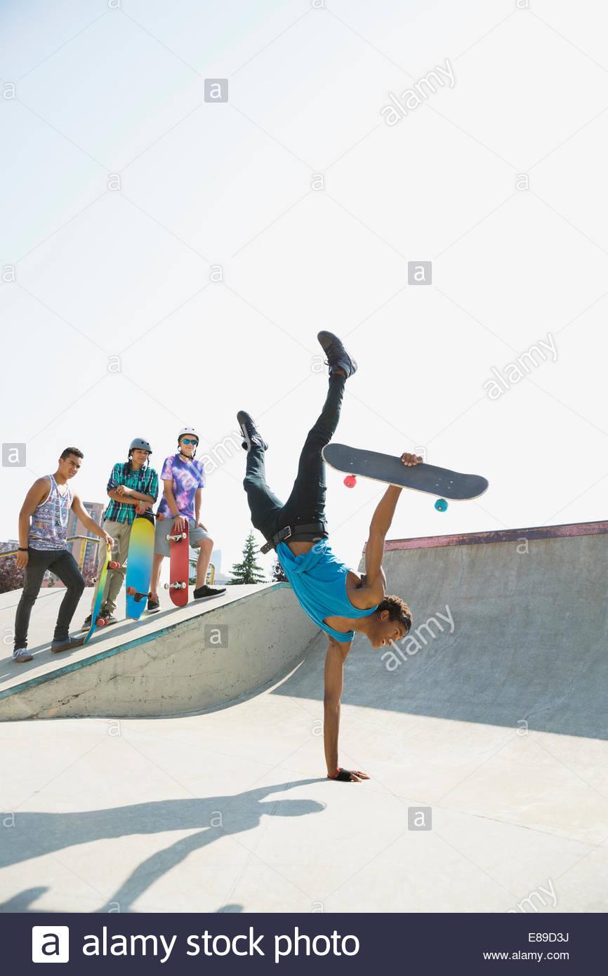 Teenage boy with skateboard doing handstand - Stock Image