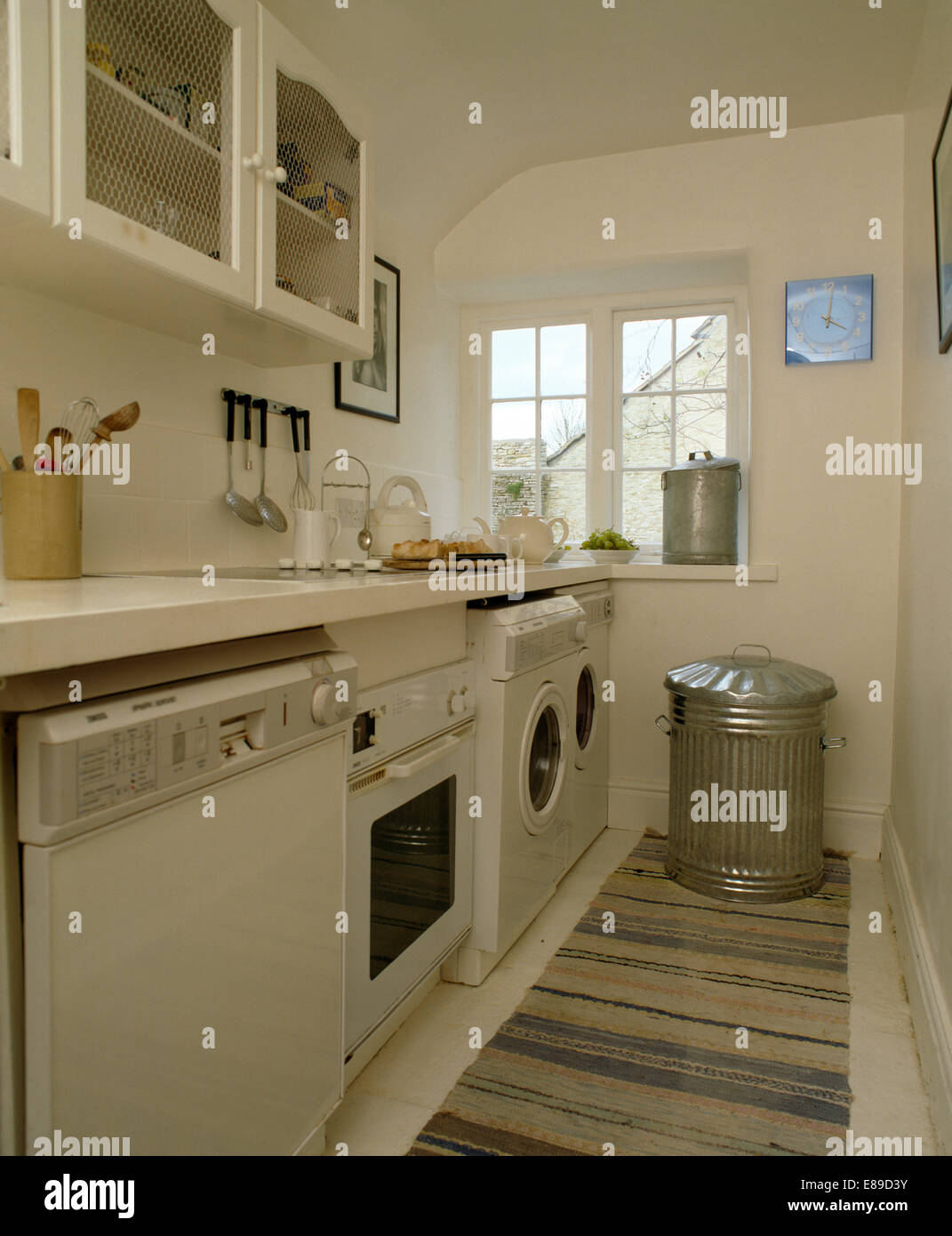 Dishwasher and oven with washing machine in row of appliances in white kitchen with galvanised bin - Stock Image