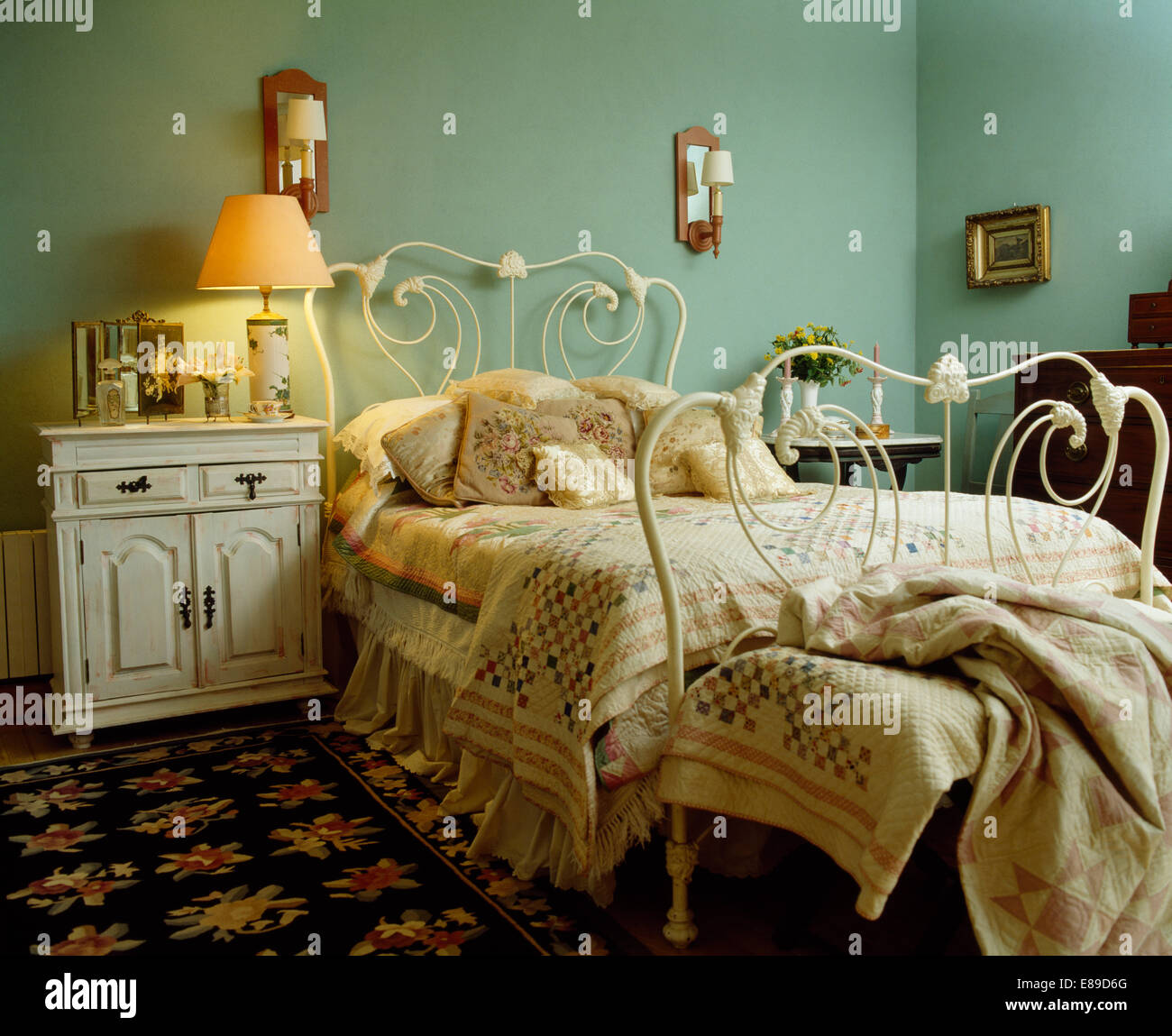 Lighted lamp beside white wrought-iron bed with patchwork quilt in pale green bedroom with floral rug - Stock Image
