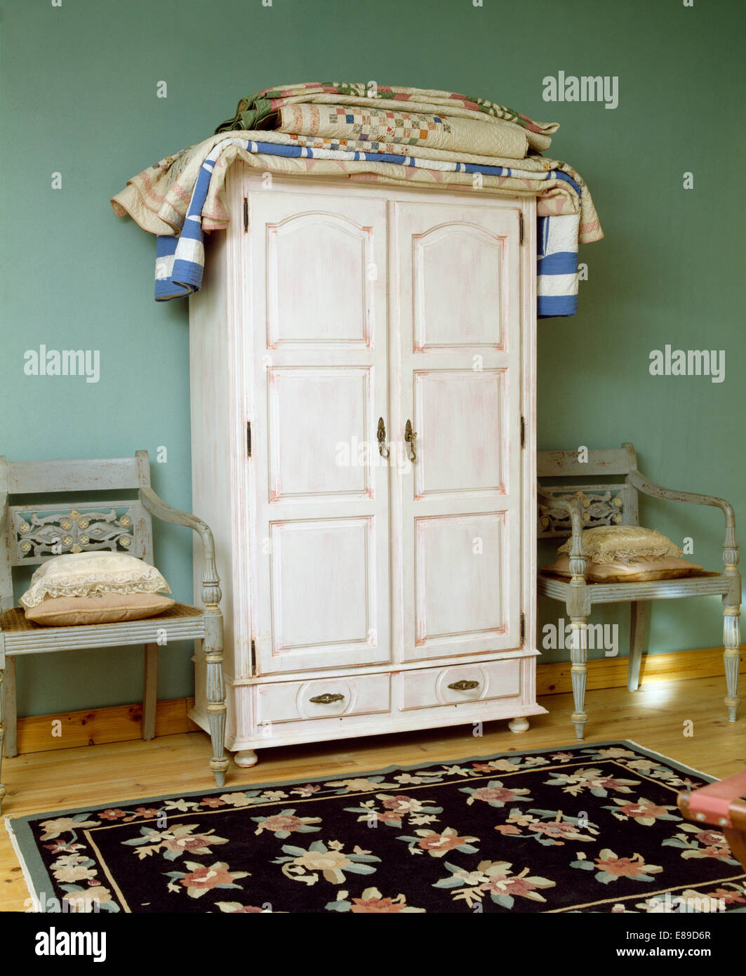 Folded Patchwork Quilts On White Painted Cupboard In Pale Green Bedroom  With Floral Rug And Pale Grey Chairs