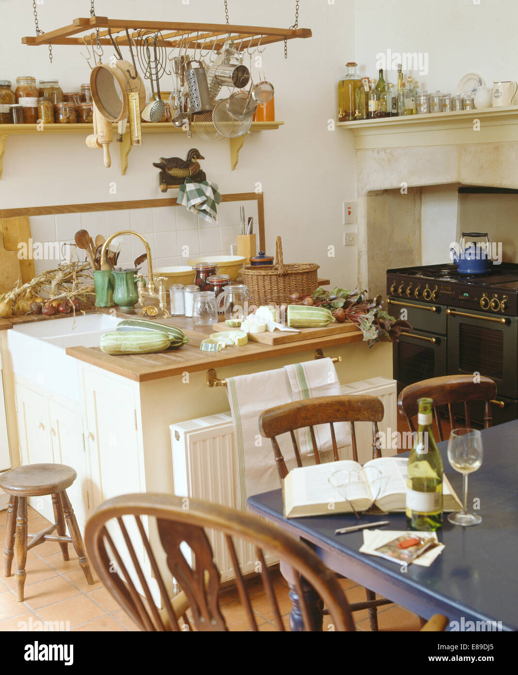 Utensils on hanging rack above island unit in country kitchen with old wooden chairs and blue painted table
