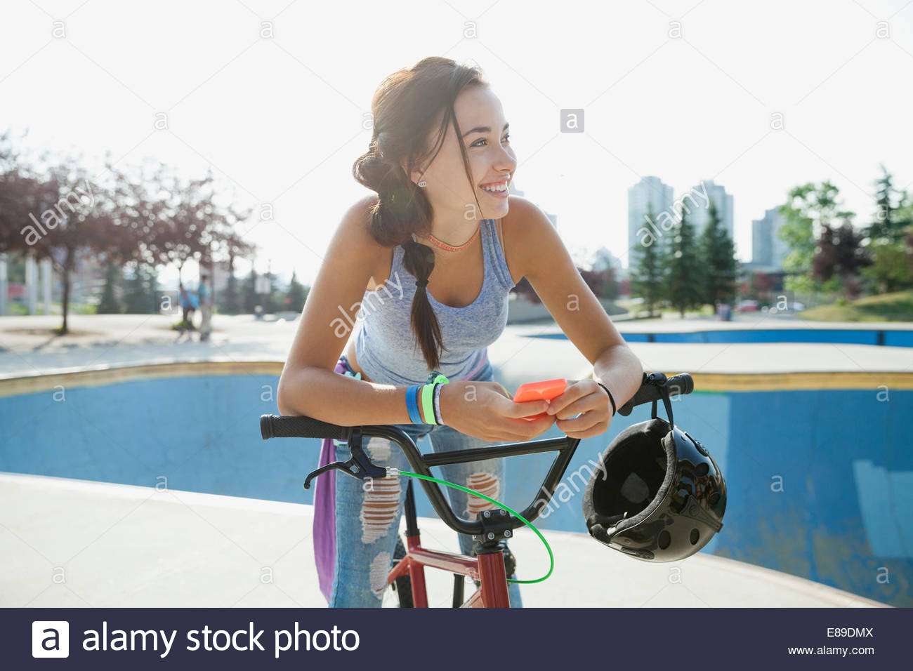 Teenage girl with cell phone on bicycle Stock Photo