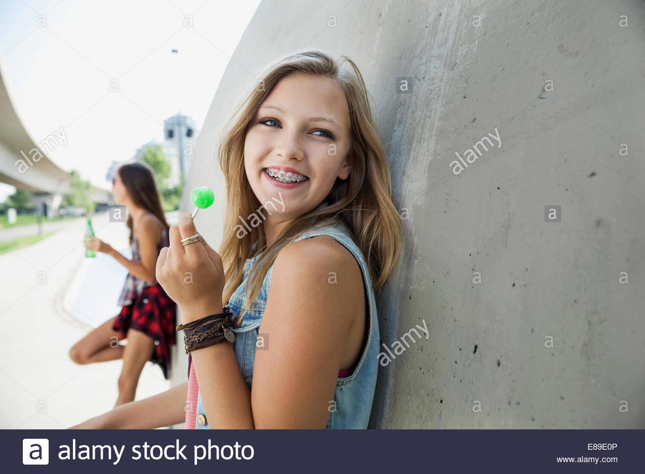 Smiling teenage girl with braces enjoying lollipop - Stock Image