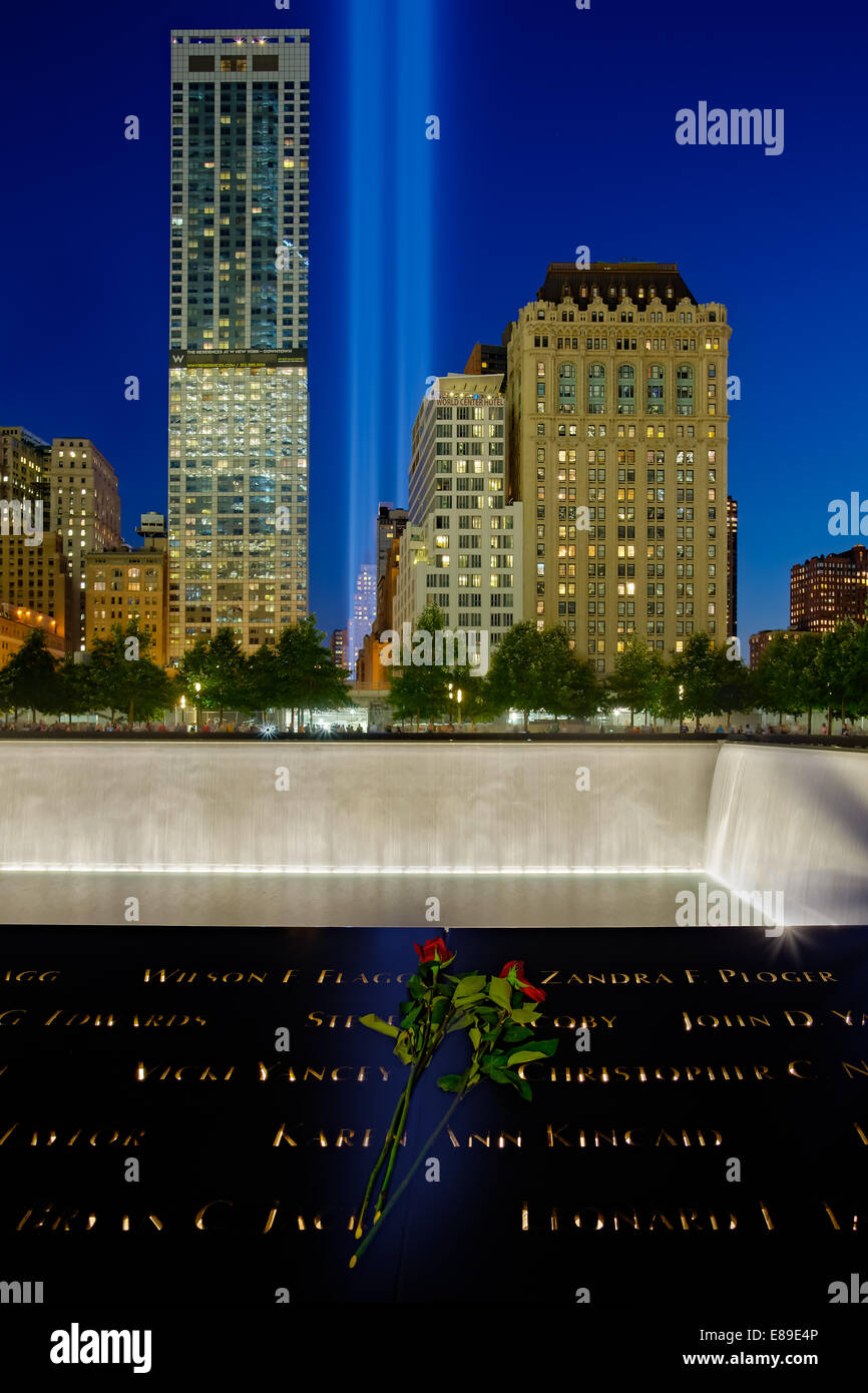 911 Tribute In Lights Memorial from Ground Zero with reflecting pool and the  beams of lights shinning high into Stock Photo