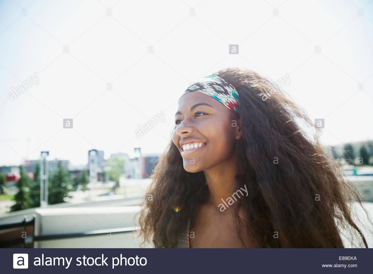 Teenage girl smiling outdoors - Stock Image