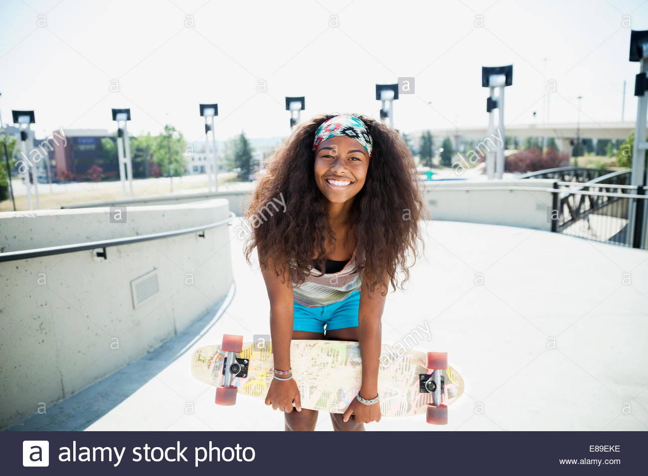 Portrait of teenage girl holding skateboard - Stock Image