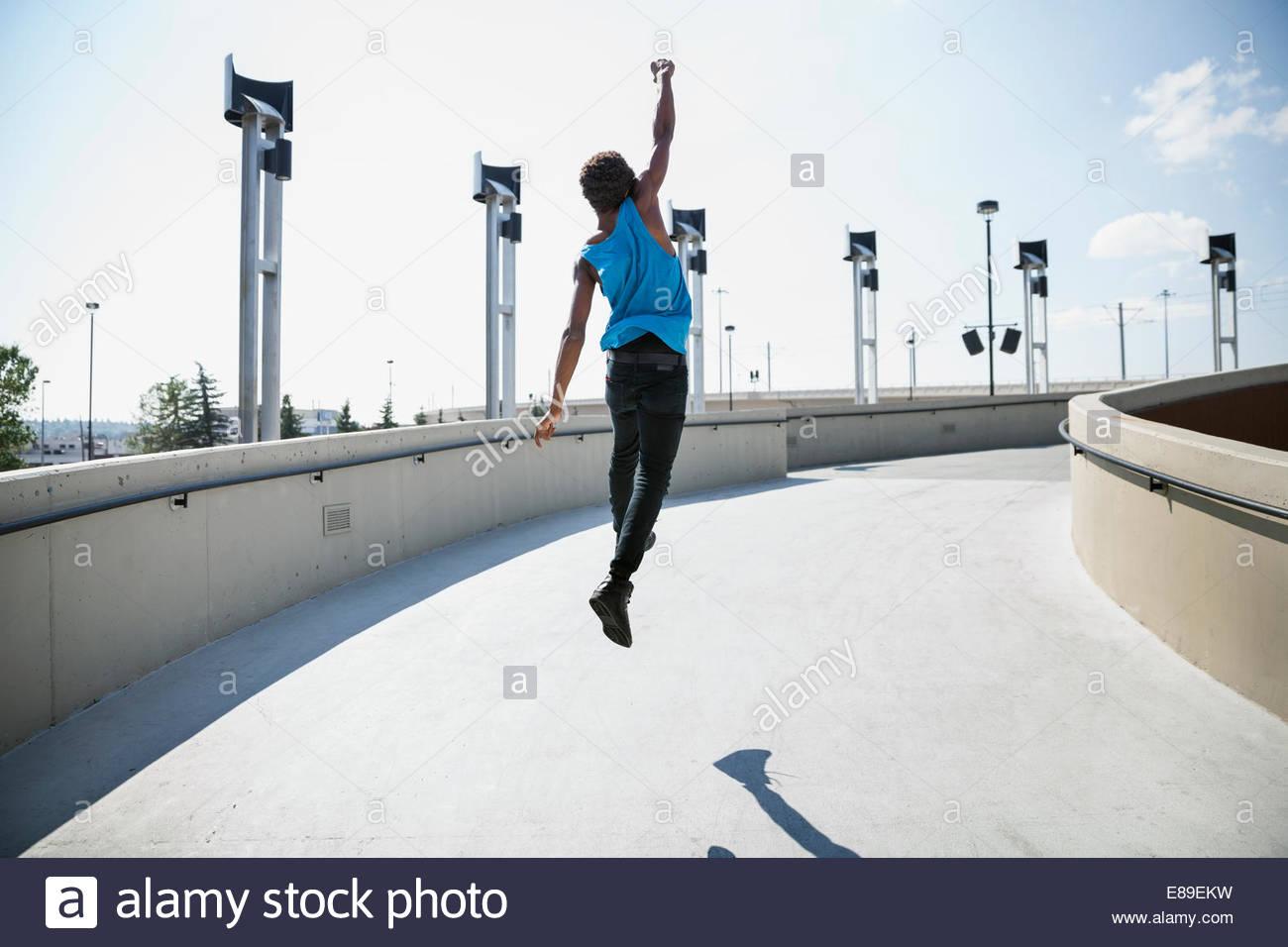 Exuberant teenage boy jumping outdoors - Stock Image