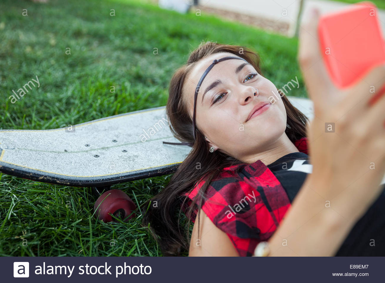 Teenage girl with cell phone laying on skateboard Stock Photo