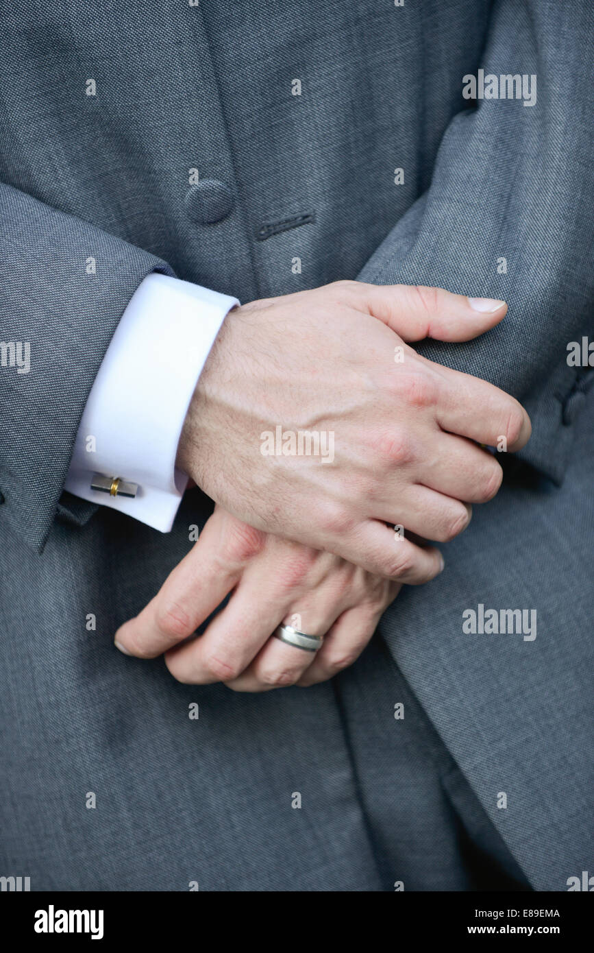 The crossed hands of a Caucasian man wearing a traditional grey morning suit, white shirt, cuff links & a wedding - Stock Image