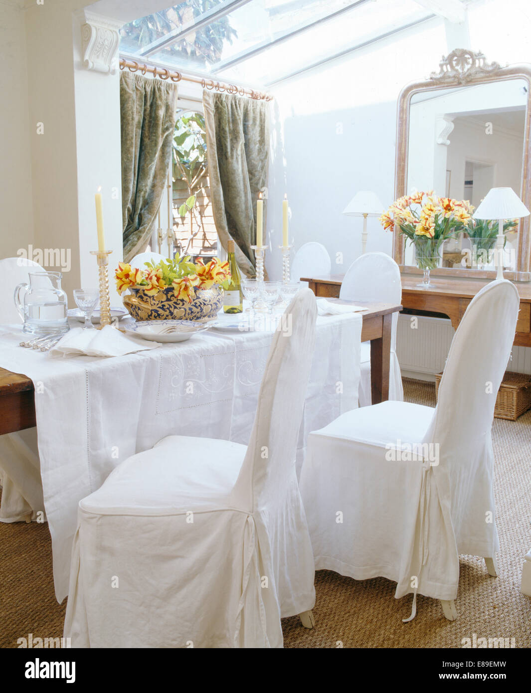 White loose covers on chairs at table with white linen cloth in ...
