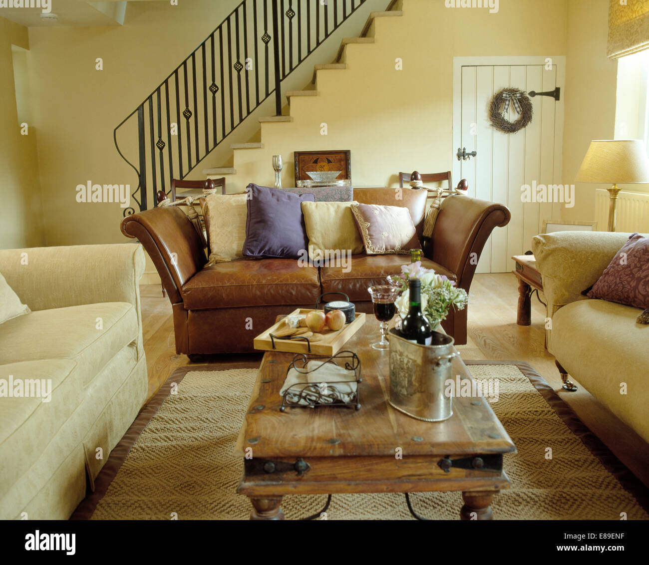Cream sofas with brown leather sofa arranged around ...