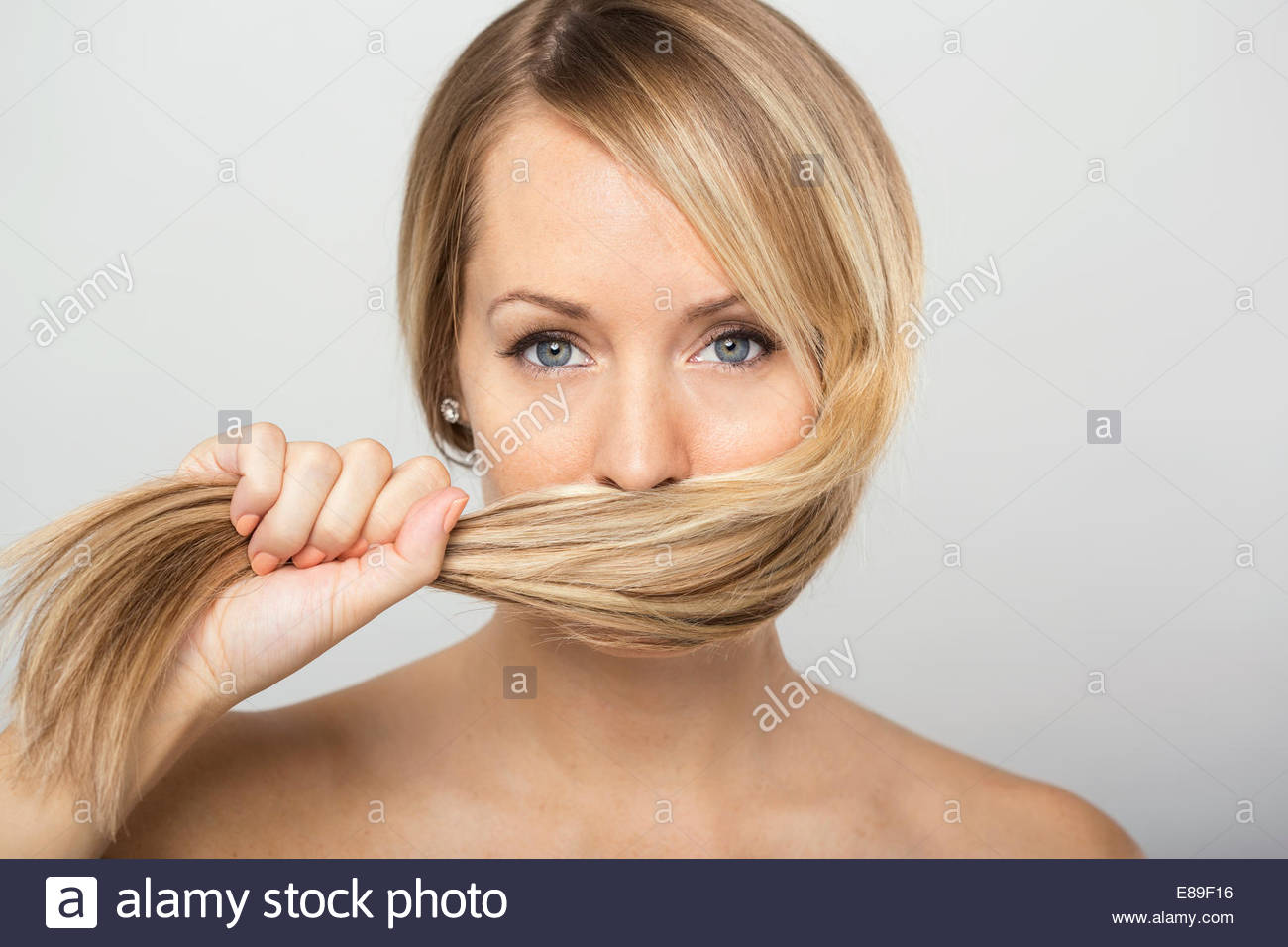 Portrait of blonde woman holding hair over face - Stock Image