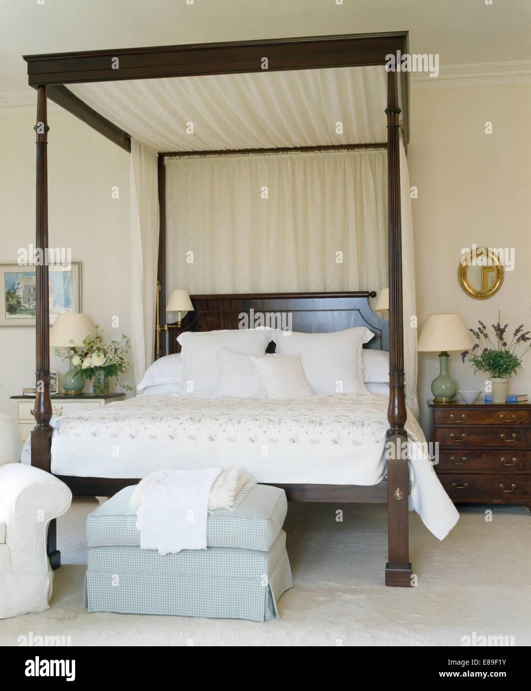 Cream drapes on dark wood four poster bed with white linen ...