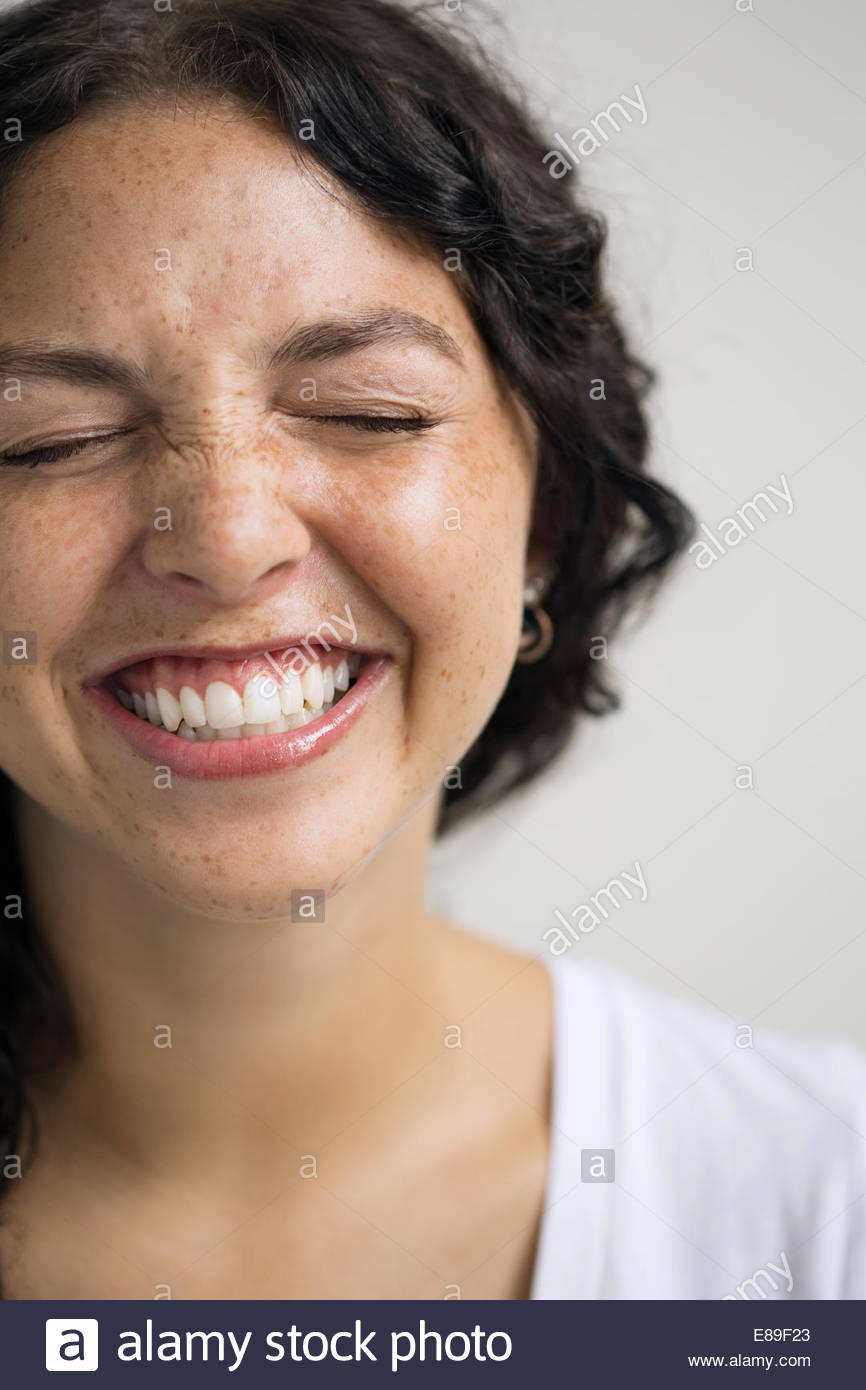 Close up of enthusiastic woman with eyes closed - Stock Image