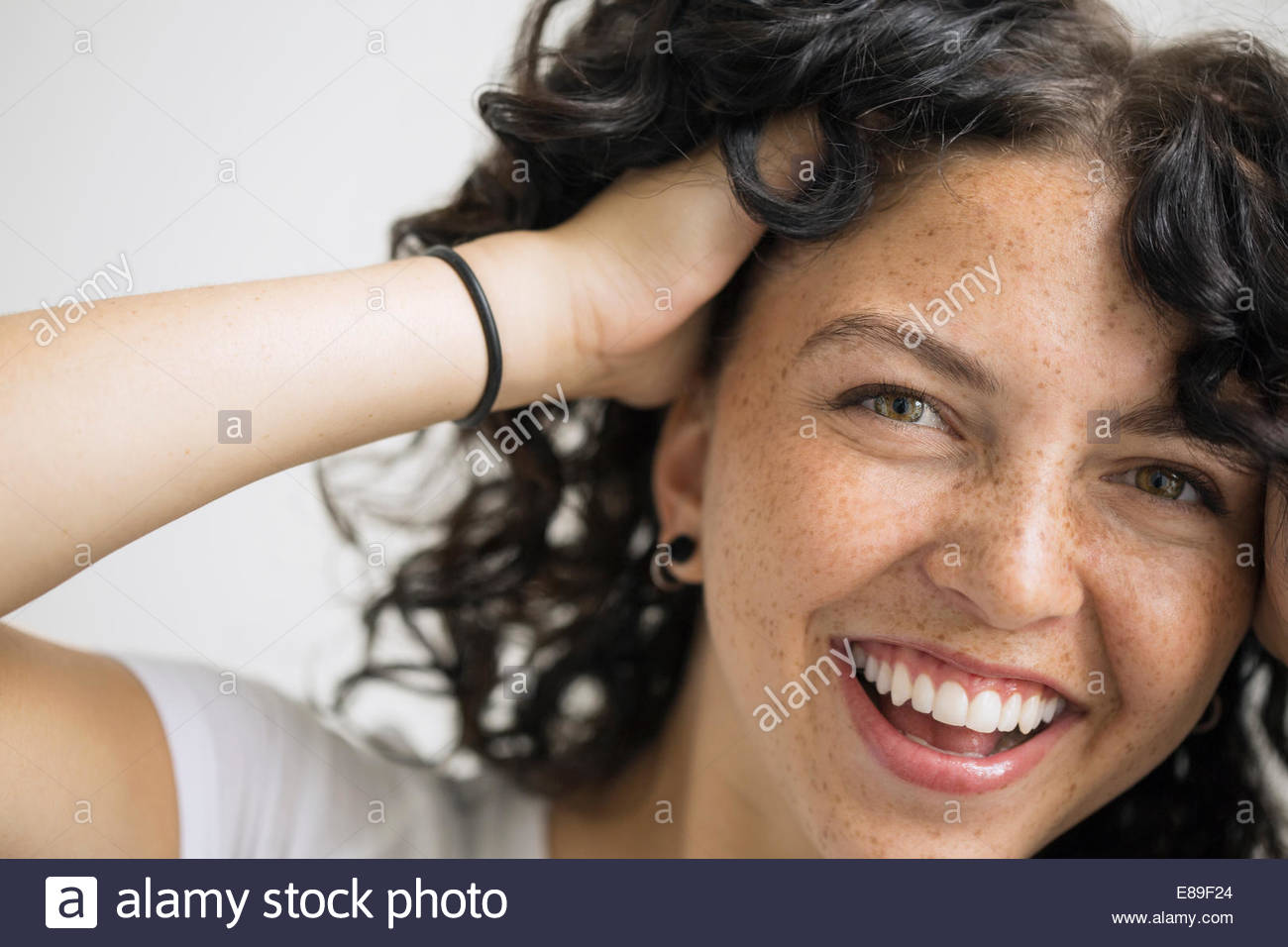 Portrait of smiling woman with hands in hair - Stock Image
